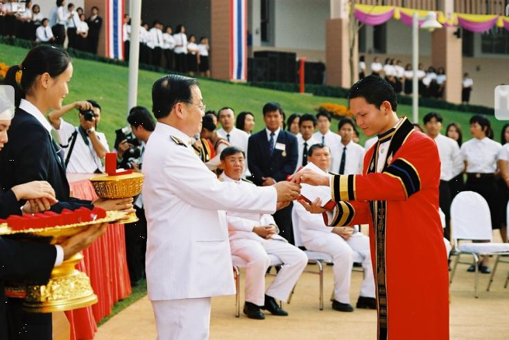 55 - รศ.ดร. วันชัย ศิริชนะ อธิการบดีมหาวิทยาลัยแม่ฟ้าหลวง มอบเข็มกลัดตราสัญลักษณ์ ให้บัณฑิตรุ่นที่ 1 (รุ่นแรก) เนื่องในพิธีพระราชทานปริญญาบัตรแก่ผู้สำเร็จการศึกษา ประจำปีการศึกษา 2545 เมื่อวันอังคาร ที่ 3 กุมภาพันธ์ 2547